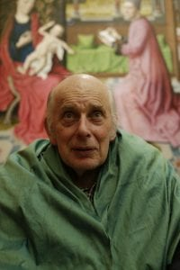 A portrait taken from a Dementia friendly creative cafe - An elderly man sitting in front of the painting St Luke Drawing the Virgin and Child by Dieric Bouts