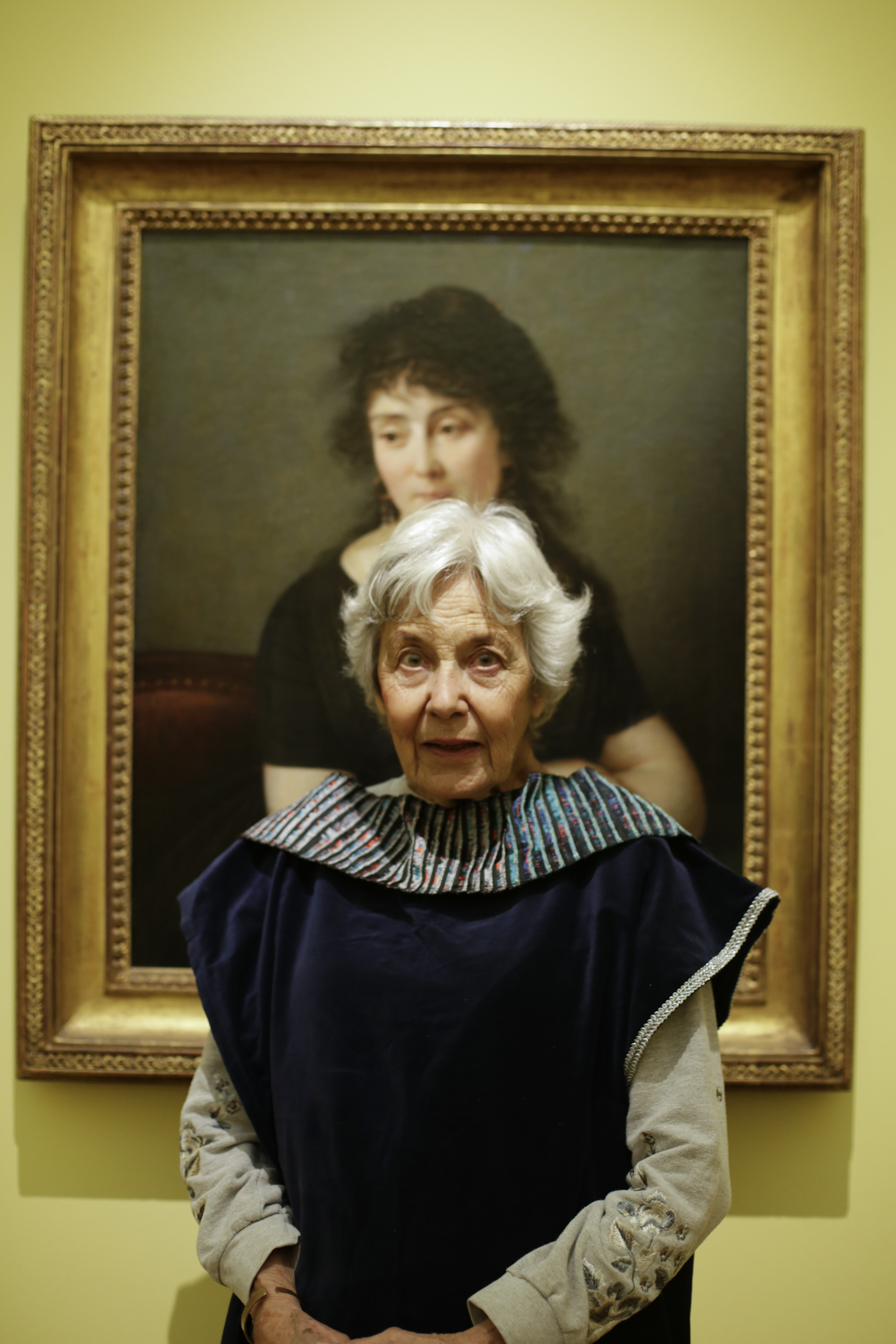 A portrait taken from a Dementia friendly creative cafe - an elderly woman sat in from of a painting in the enlightenment gallery
