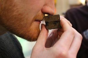 A man with a beard sniffing a miniature cube of tea designed to look like Ai Weiwei's Ton of Tea