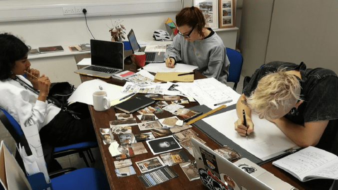 Anika, Marcin and Maisie working around a large table covered in photographs and paperwork