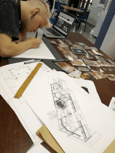 Marcin working next to a 3D sketch of the gallery design