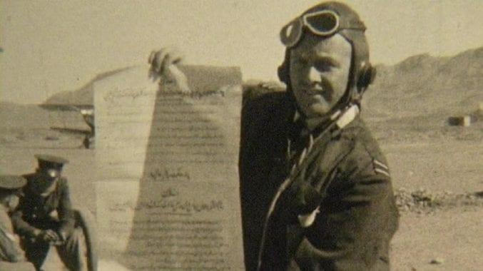 Pilot holds up leaflet before a flight, 1930s