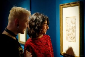 A man and a woman smile as they look at one of Leonardo's sketches in the exhibition.