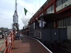 Steam train outside the M Shed. Train driver waves the flag ready to go.
