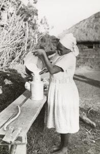 A Kikuyu woman dressed in white pouring milk into a jug