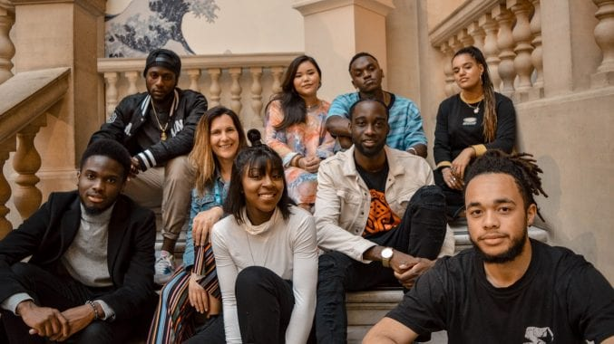 Photograph of a group of young people sat on the steps of the museum