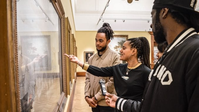 A group of young people looking at a painting in a gallery