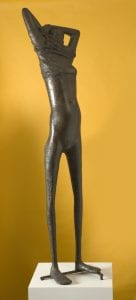 A standing female human figure removing her clothes, cast in bronze by Reg Butler