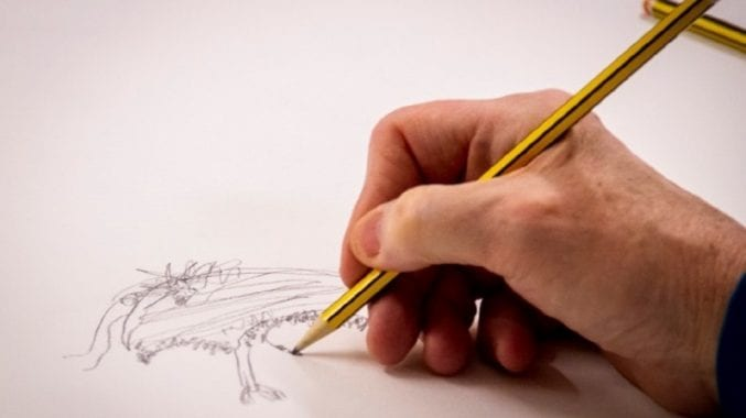 A hand holding a pencil and sketching on a piece of paper