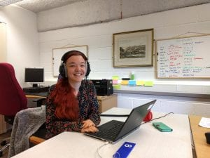 Smiling woman wearing headphones sat in front of a laptop
