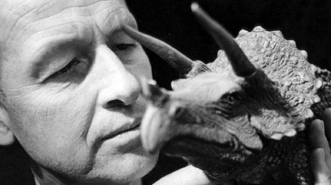 Ray Harryhausen holding a model of a triceratops