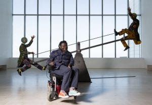 "Yinka Shonibare sat in front of ""End of Empire"" at Turner Contemporary"