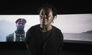 "John Akomfrah stood in front of his work ""Mimesis: African Soldier"" at the Imperial War Museum"