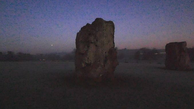 A screenshot from the Mary Flower film. Two large ancient stones standing against the horizon at dawn