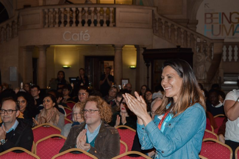 Photograph of audience applauding at uncomfortable truths launch, along with Claire Simmons, Youth Engagement officer at Bristol museum and Art gallery