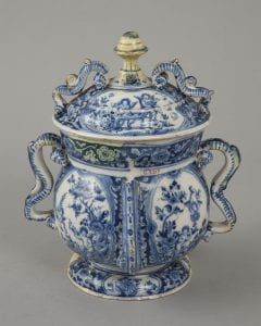 A Delftware posset pot with elaborate handles and a blue and white design
