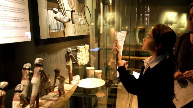 A school girl examining objects in the Egypt gallery at Bristol Museum