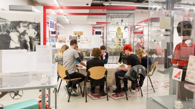 A group of school children sat around a table inside one of the M Shed galleries