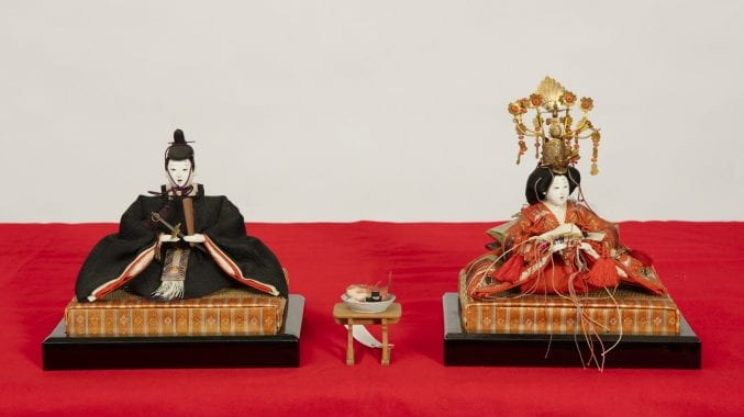 Emperor and Empress figures sat on top of a red cloth. Part of Japanese Doll Festival.