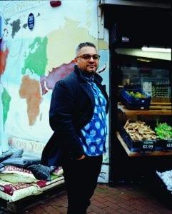 Man ( Nikesh Shukla) standing by market stall