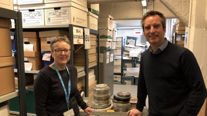 Photograph of a man and a woman standing in a store room in front of reels of film
