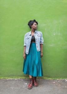 Image of woman (Vanessa Kisuule) against a wall.
