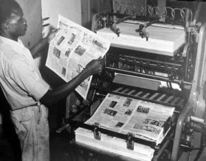 machine operator checks the inking on a page of newsprint