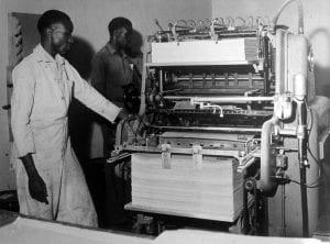 Two men check newspaper printing press