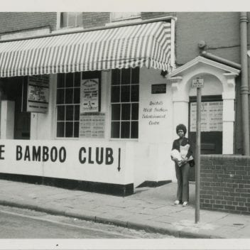 a woman stands outside the bamboo club