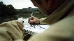 A street artist sketching with a black sharpie
