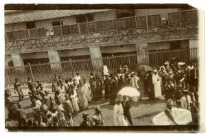 Photograph of a large crowd of people in Ghana taking part in a masquerade dressed in British costume