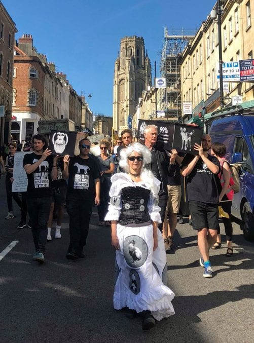 Melanie Ruth wearing her customised wedding dress leading a crowd of protesters down Park Street in Bristol