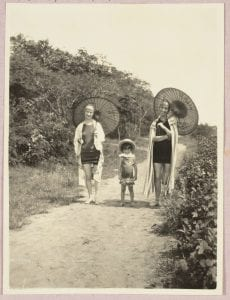 Photograph of two women and a child at the beach carrying Chinese parasols.