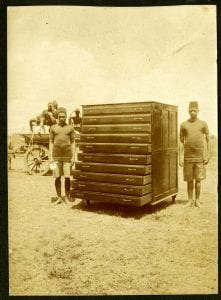 Photograph of two Kenyan apprentice carpenters standing either side of a large chest of drawers.