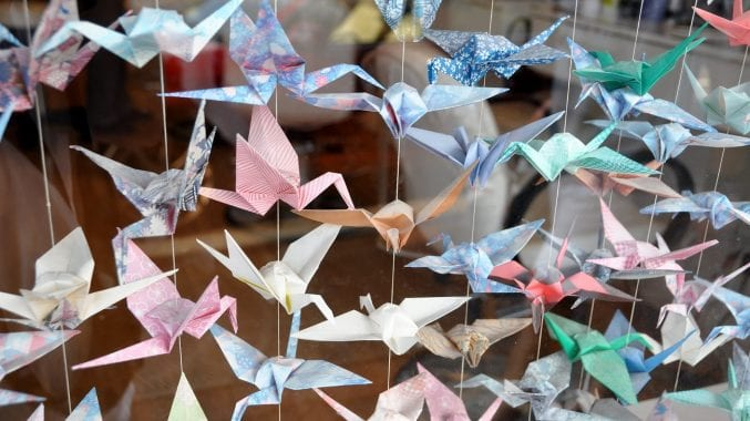 Several brightly coloured origami cranes threaded together