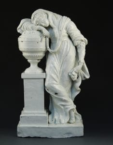 A statue of a woman leaning against a vase