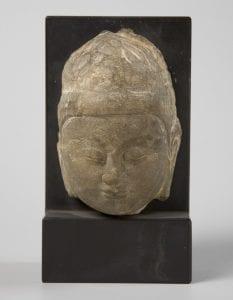 A stone Buddha head on a black mount