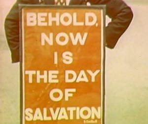 A sandwich board that reads 'Behold now is the day of salvation'