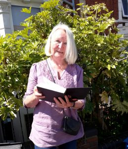 Archives volunteer, Pat Ellingham holding a copy of Imogen Lycett Green's book about her trip to India following in Penelope's footsteps