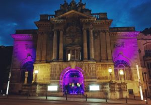 The exterior of Bristol Museum & Art Gallery at night lit with purple lighting in solidarity with Minneapolis