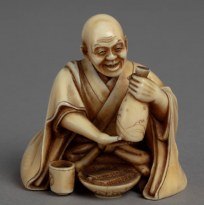 Ivory carving of seated man in kimono holding a bottle of rice wine.