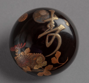 Circular lacquer netsuke with design of chrysanthemums and long life symbol.