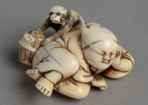 Ivory netsuke carving of a man in kimono asleep as monkey steals fruit behind his back.