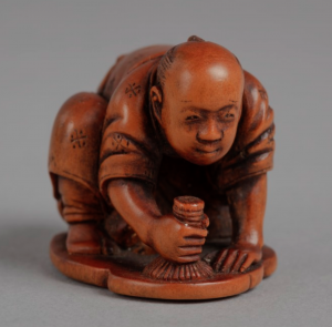 Wooden netsuke carving of man in kimono on hands and knees polishing the floor.