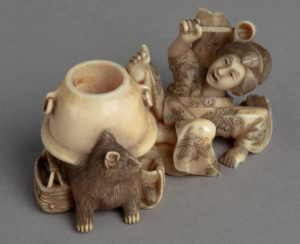 Ivory carving of a Japanese woman falling back in surprise as a water pot transforms into a raccoon.