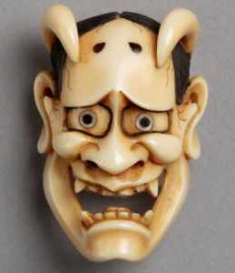 Ivory netsuke carving in the form of a theatre mask depicting a demonic woman with horns.