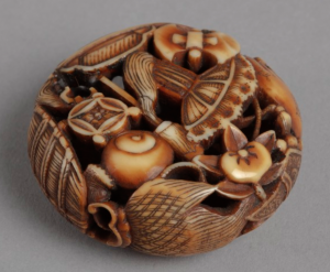 Flattened circular ivory netsuke carving comprised of lucky symbols.