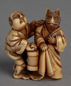 Ivory netsuke carving, man in kimono carrying lantern next to fox in kimono.