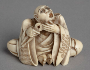 Ivory netsuke carving of seated man in kimono extracting his own tooth with pliers.