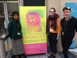 Young Exhibition Producers Anika, Maisie and Marcin in front of exhibition signage for Leonardo Unfinished exhibition at Bristol Museum & Art Gallery